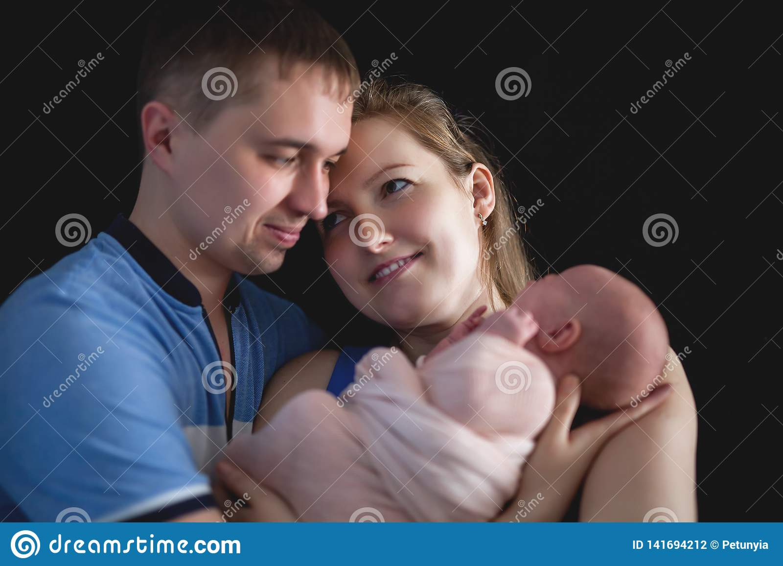 De vader en de moeder houden een baby, het pasgeboren concept van de Familiezorg