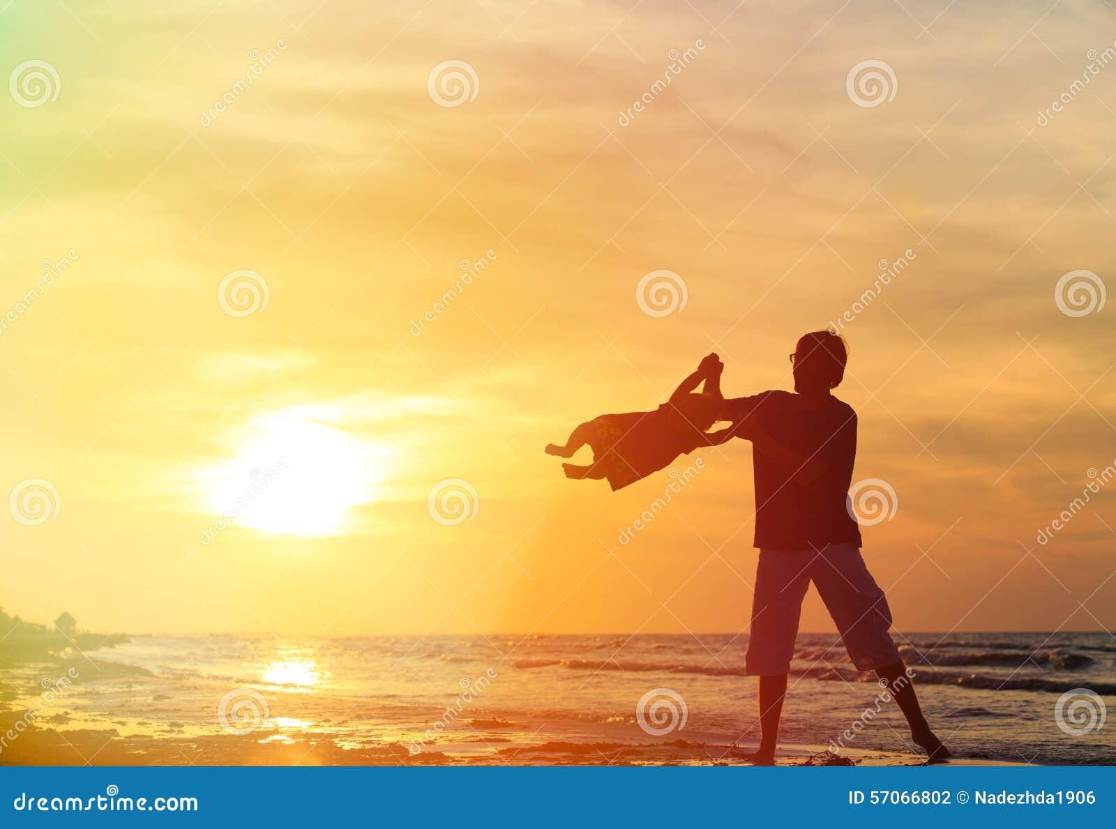 De vader en weinig dochter silhouetteren op strand