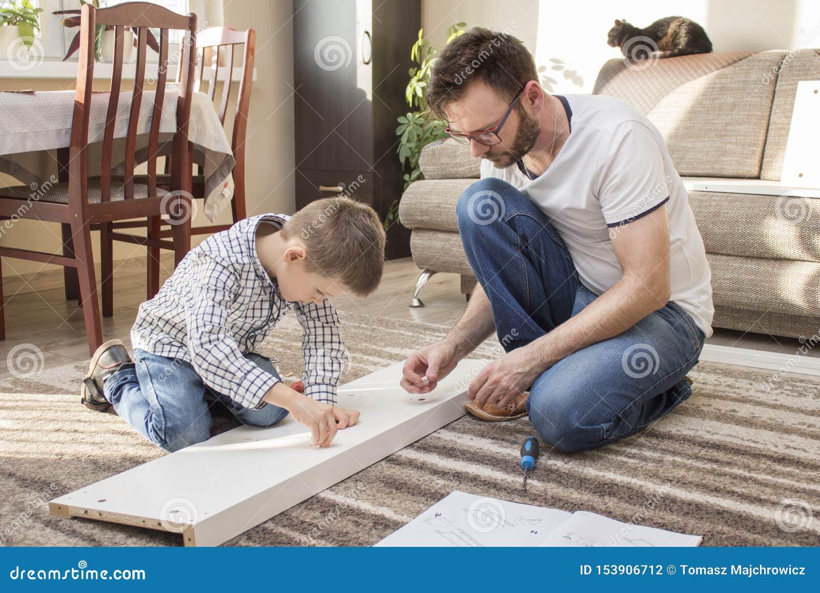 De vader en de zoon brengen meubilair samen De vader geeft zijn zoonselementen en de jongen zet hen in de juiste plaatsen