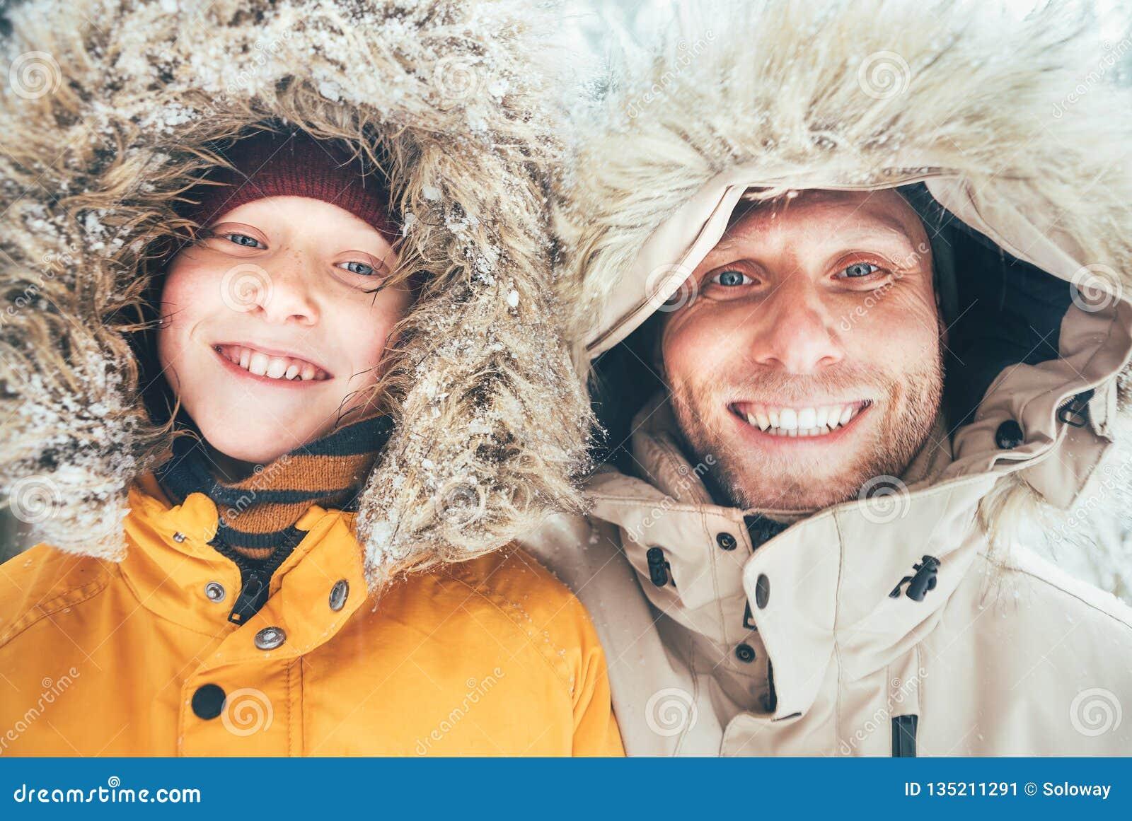 De vader en de zoon kleedden zich in de Warme Toevallige Bovenkleding Met een kap van het Parkajasje lopend in sneeuw bos vrolijk