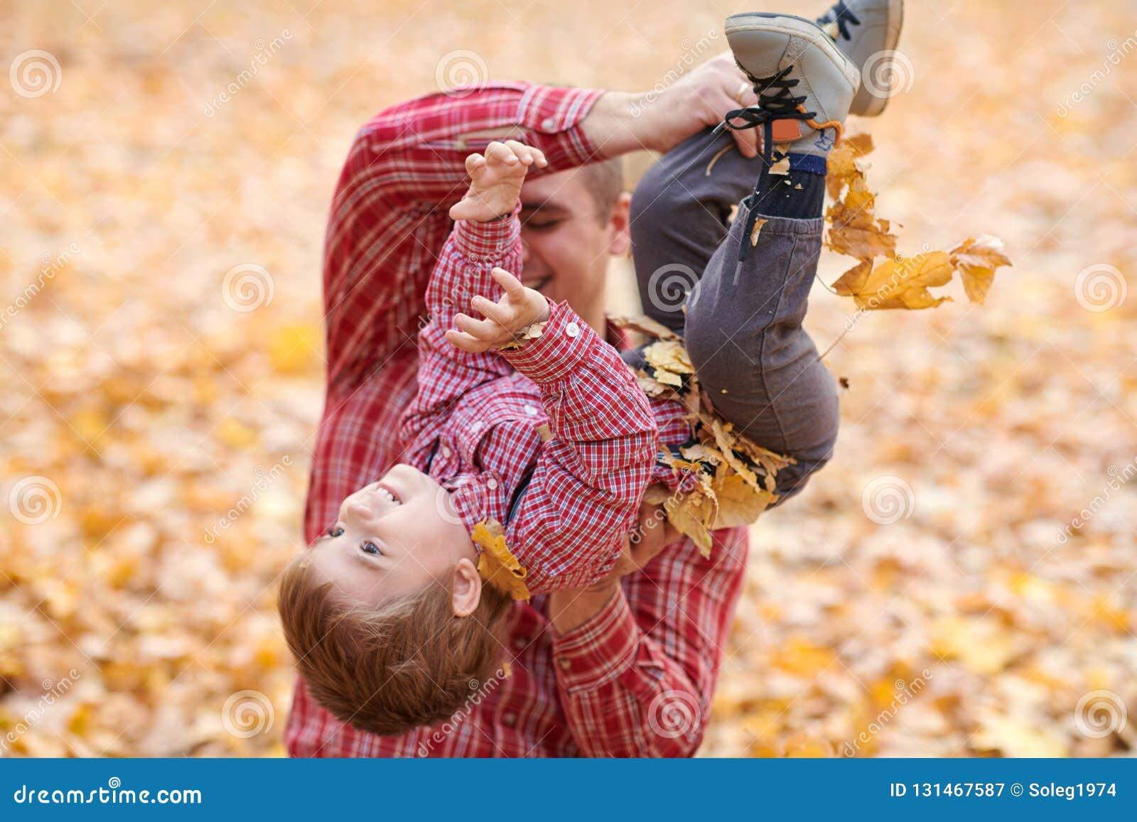 De vader en de zoon spelen en hebben pret in het park van de de herfststad Zij die, het glimlachen, het spelen stellen Heldere ge
