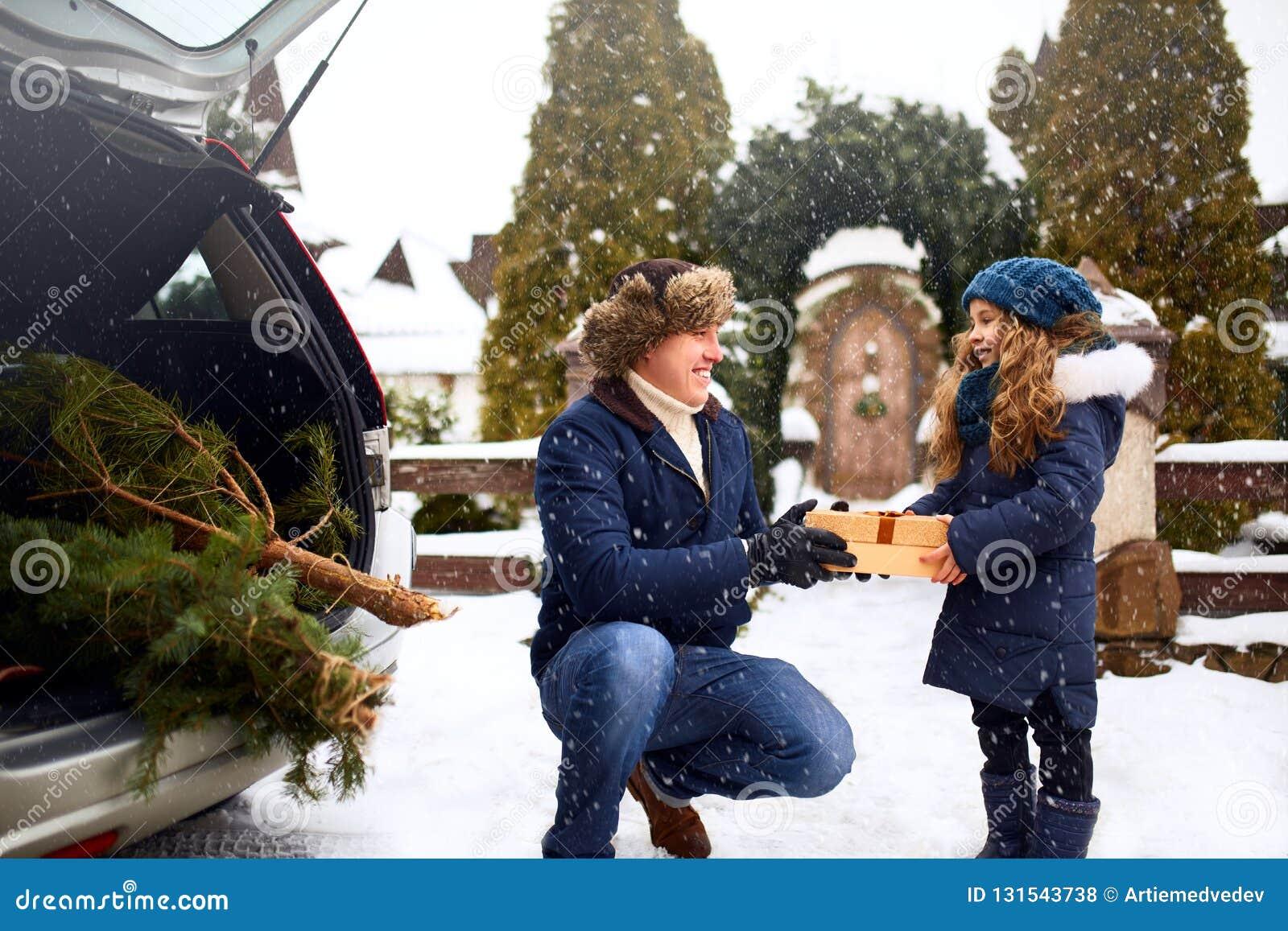 De vader stelt dochter voor een giftdoos in openlucht op sneeuw de winterdag Kerstboom in grote boomstam van familieauto Meisje