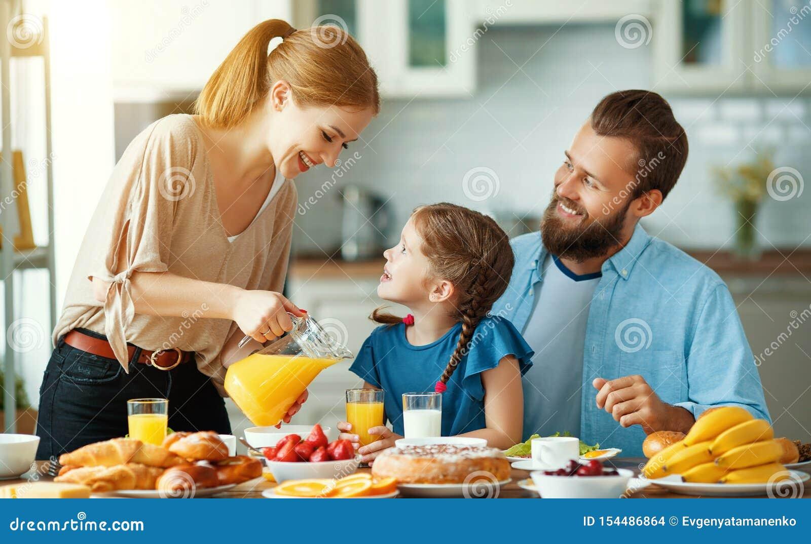 De vader van de familiemoeder en de kinddochter hebben Ontbijt in keuken in ochtend