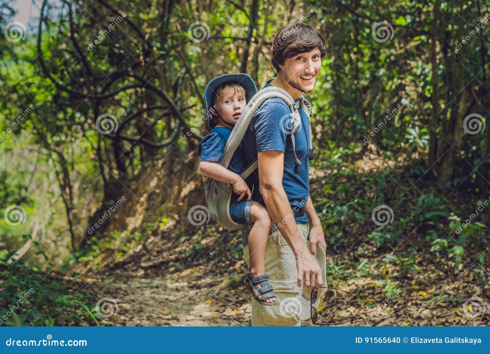 De vader vervoert zijn zoon in baby het dragen wandelt in F