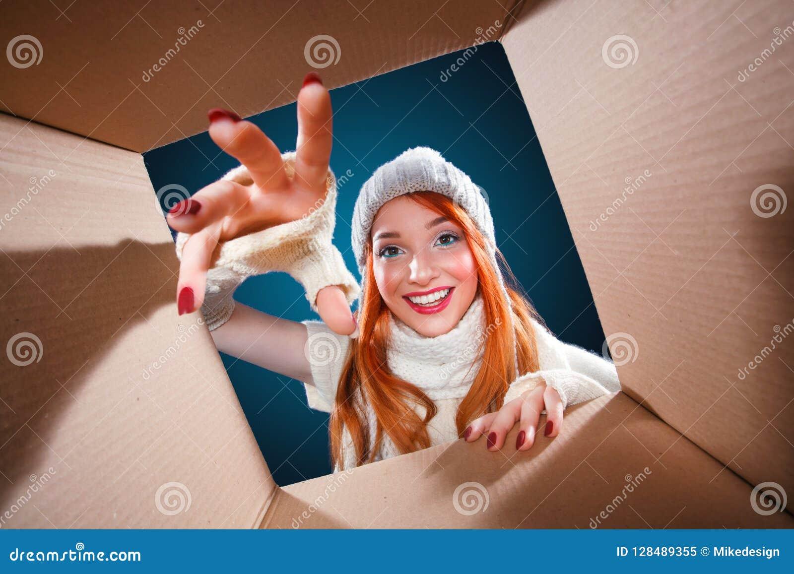 De vakantie van Kerstmis en van het Nieuwjaar De gelukkige doos van de vrouwen open gift op de winterachtergrond met lichten