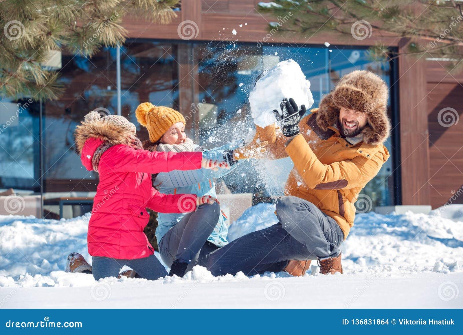 De vakantie van de winter Familietijd die samen in openlucht werpend sneeuw het vechten het lachen verrast close-up zitten