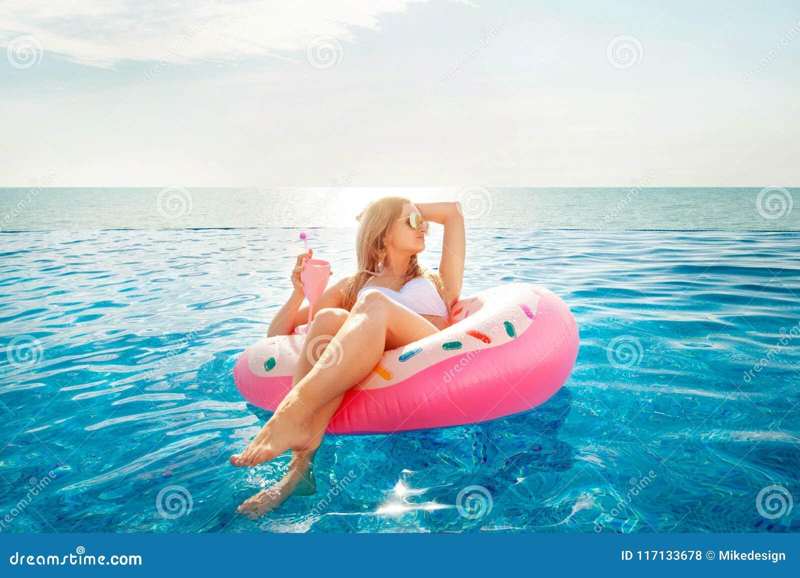 De vakantie van de zomer Vrouw in bikini op de opblaasbare doughnutmatras in het KUUROORD zwembad