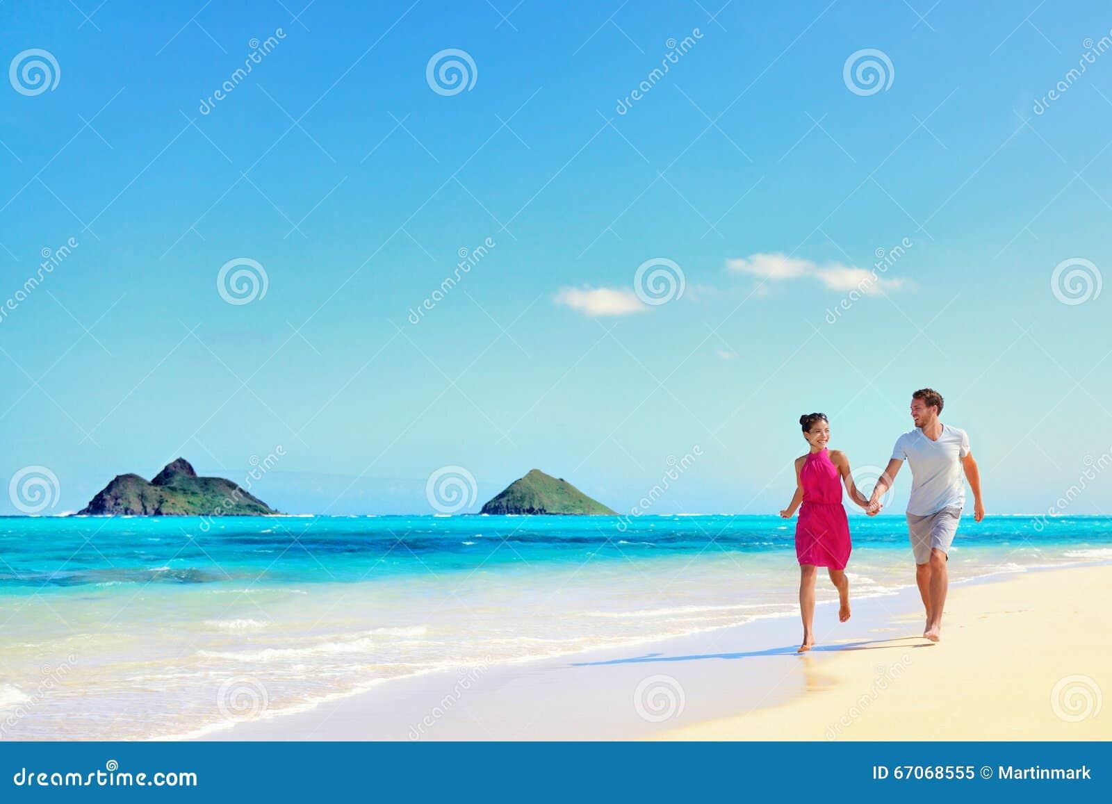 De vakantiepaar die van Hawaï op turkoois strand lopen