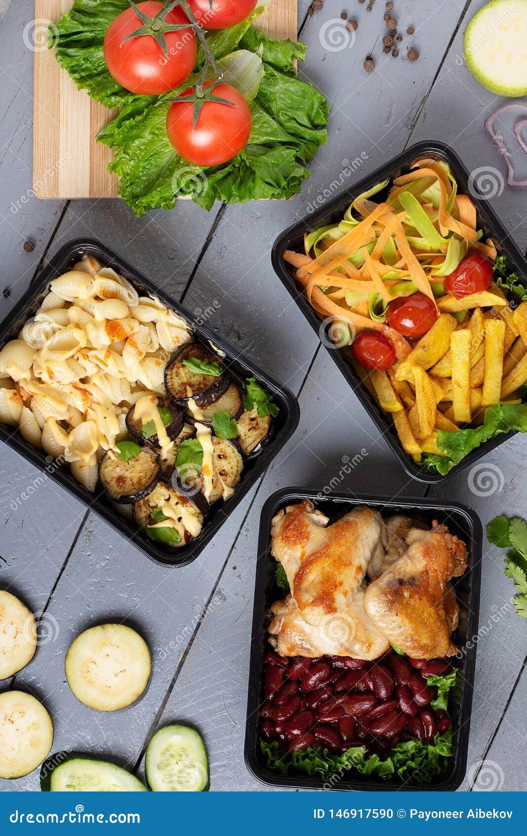 De vakjes van de voedselcontainer en, rauwe groenten, zuchini en aubergines, wortel en ui op grijze lijst