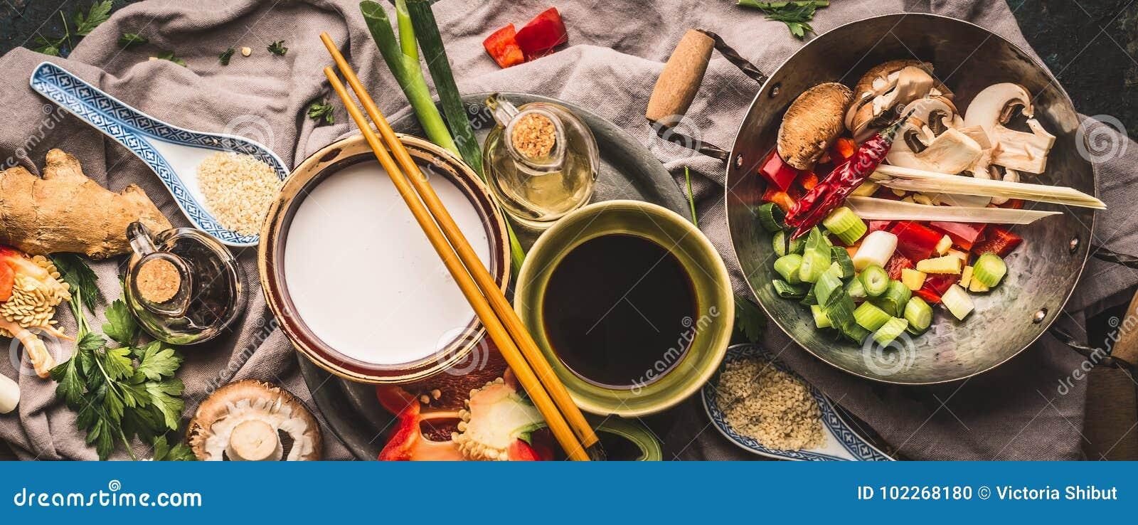 De vegetariër beweegt gebraden gerechtingrediënten: gehakte groenten, kruiden, kokosmelk, sojasaus, wok en eetstokjes, hoogste me