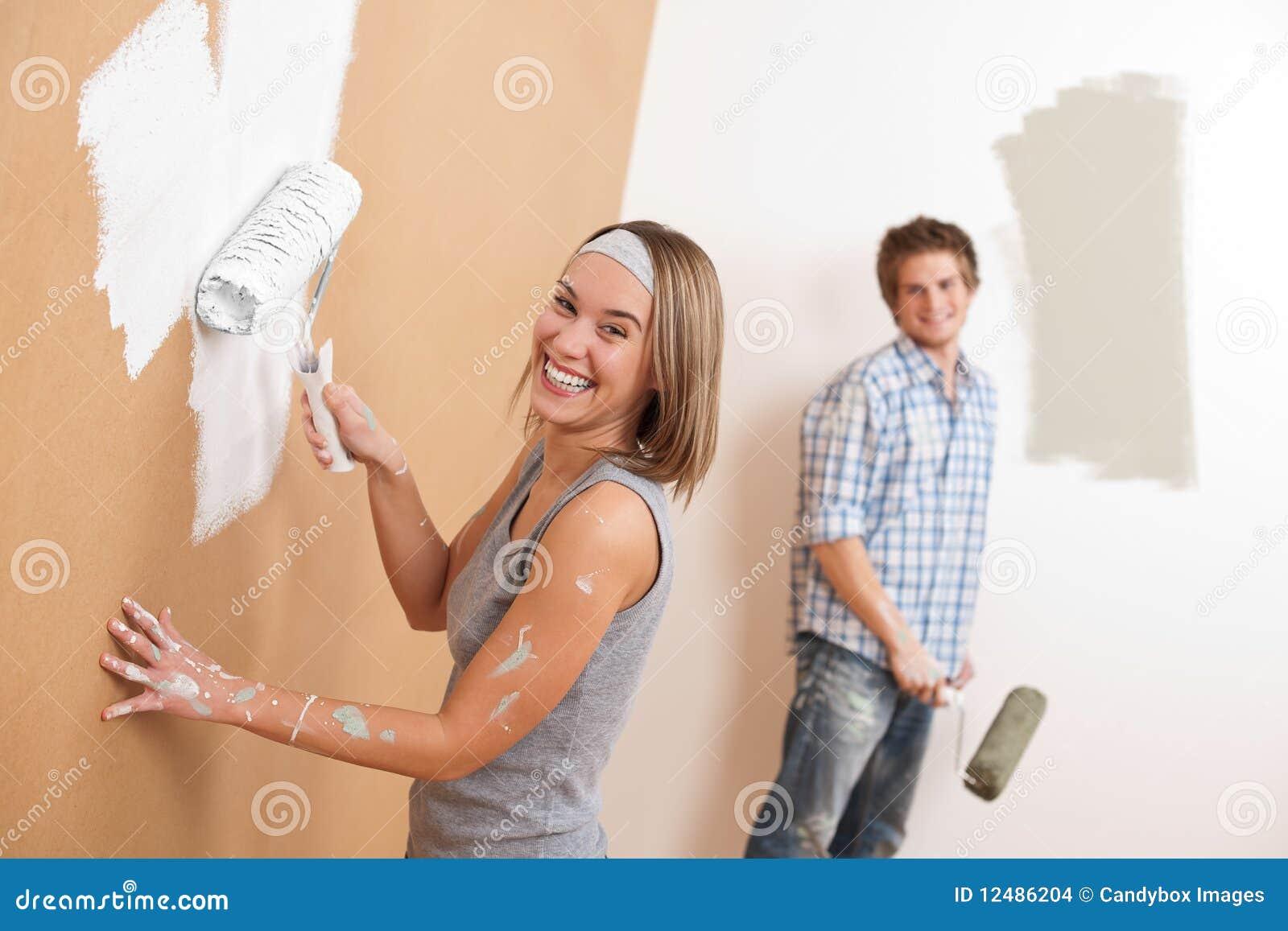 De verbetering van het huis: Jonge paar het schilderen muur