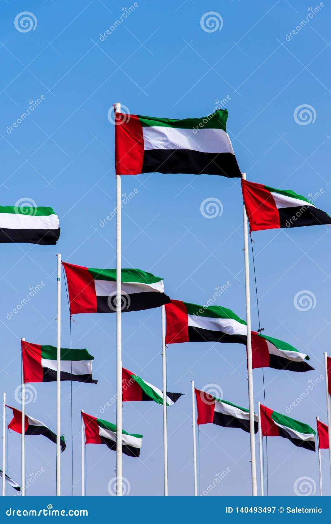 De verenigde Arabische vlaggen die van Emiraten in de wind tegen blauwe hemel winden