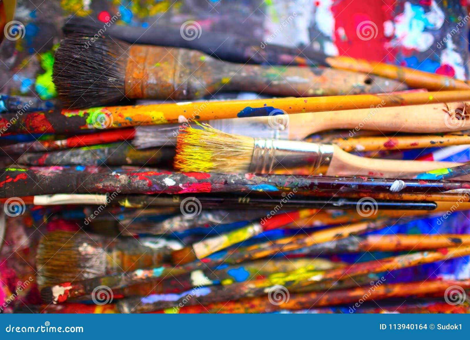 De verfborstels van verschillende die grootte, door levendige kleuren worden bevlekt, sluiten