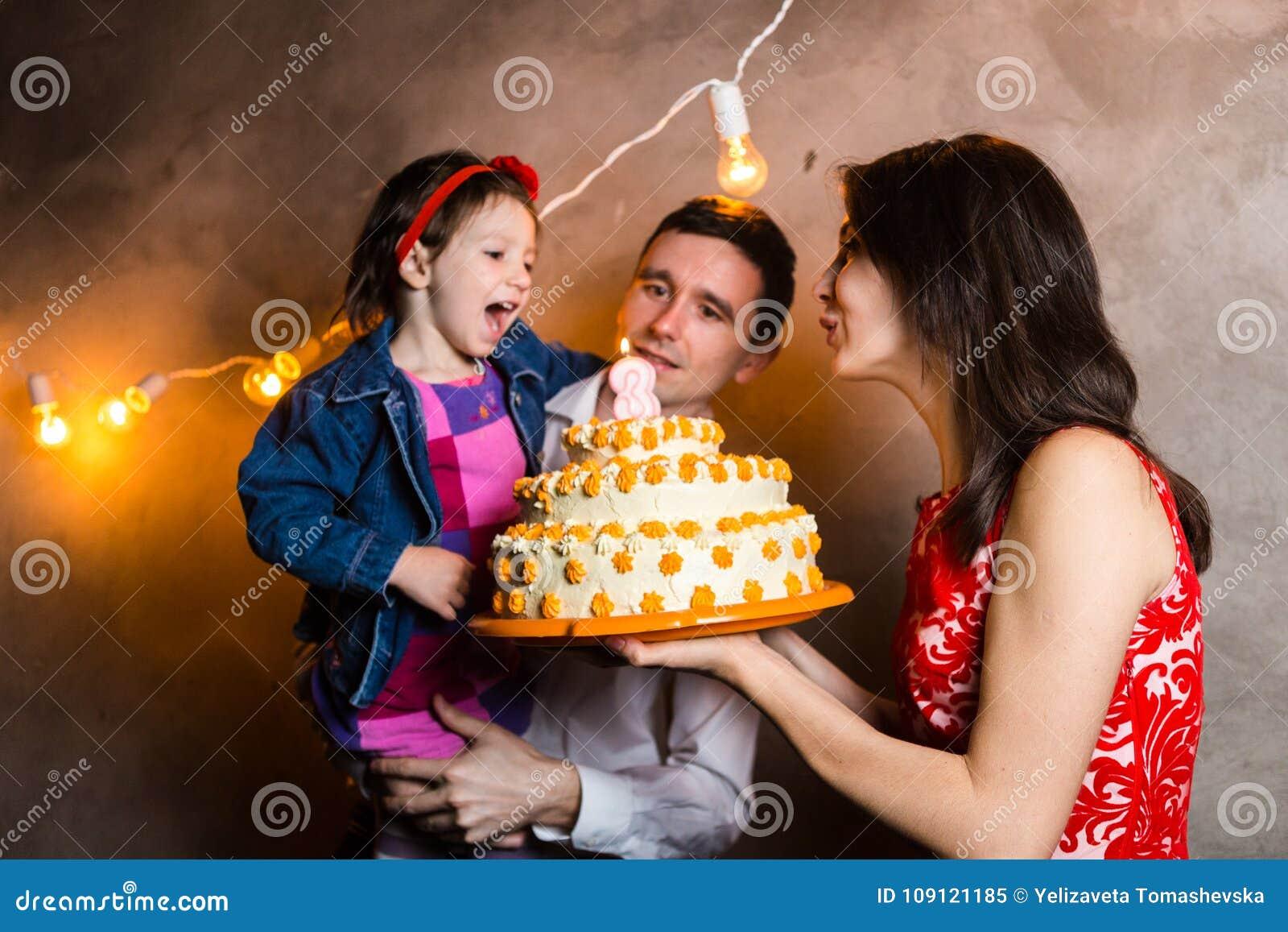 De verjaardag van de vakantiekinderen van de themafamilie en het blazen uit schouwen op grote cake jonge familie van drie mensen