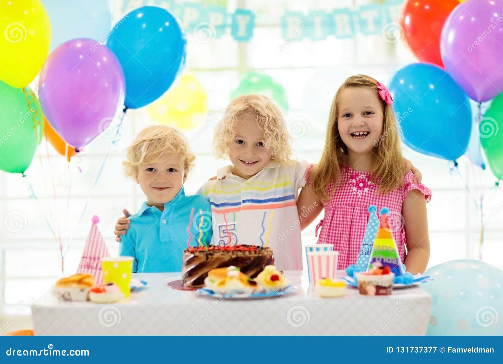 De verjaardagspartij van jonge geitjes Kind het blazen uit schouwt op kleurrijke cake Verfraaid huis met de banners van de regenb