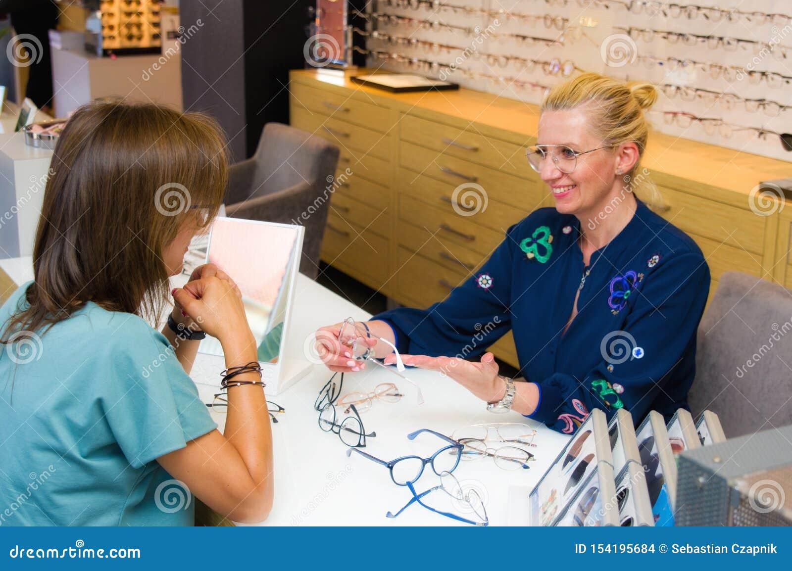 De verkoopster van de opticiensalon met haar cliënt die oogglazen kiezen