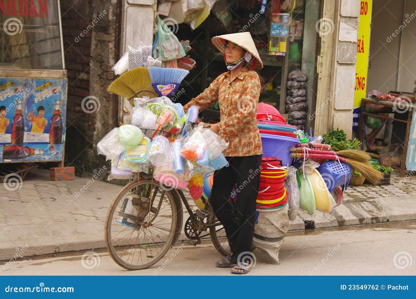 De verkopende bezems van de vrouw en plastic voorwerpen