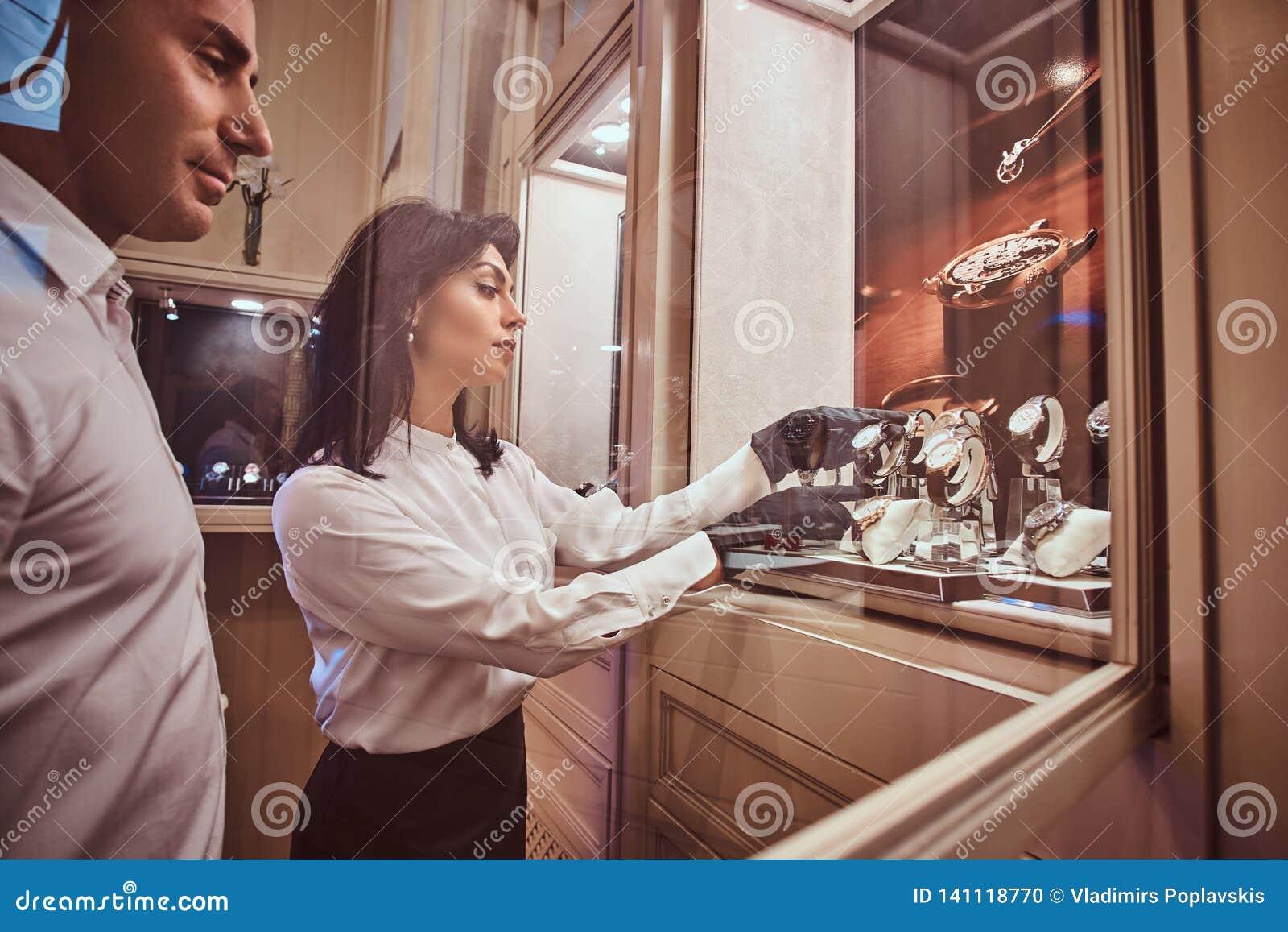 De verkoper toont de cliënt een exclusief horloge die van mensen zich naast open showcase bevinden