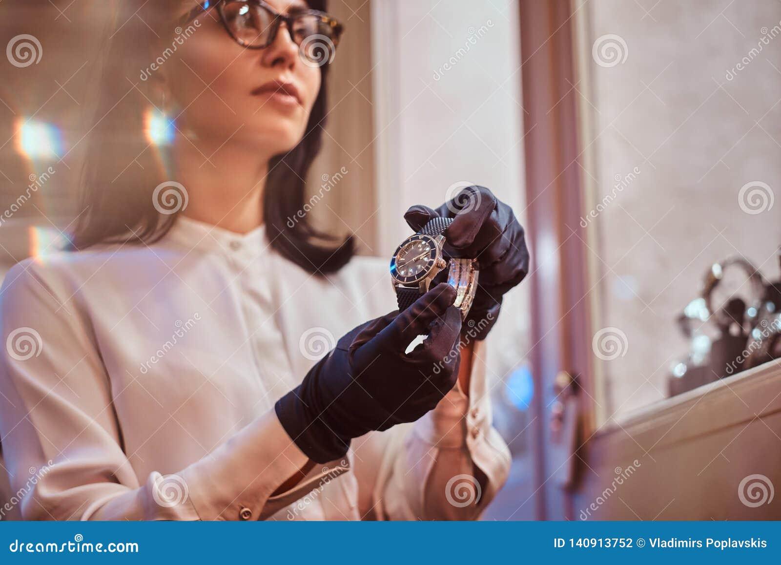 De verkoper toont een exclusief polshorloge van mensen van de nieuwe inzameling in de opslag van luxejuwelen