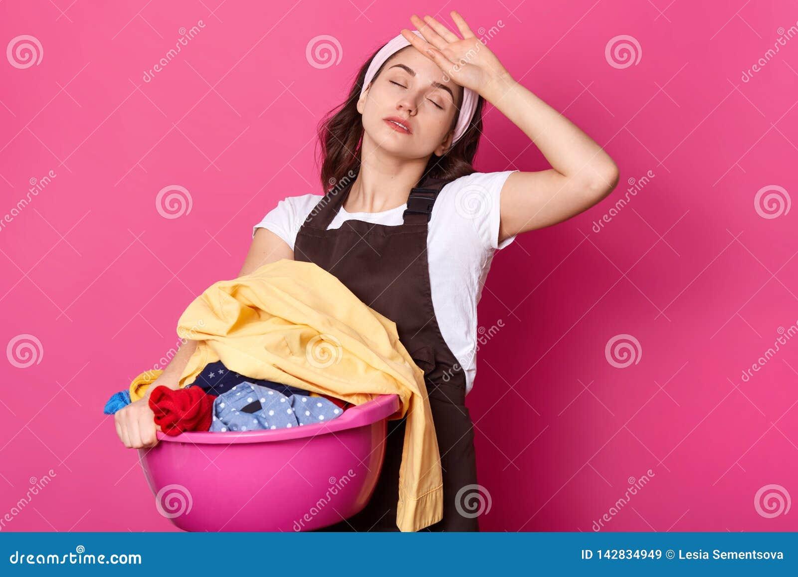 De vermoeide bezige Europese vrouw houdt bassin met vuile kleren, houdt ogen gesloten, treft voor was voorbereidingen, draagt hoo