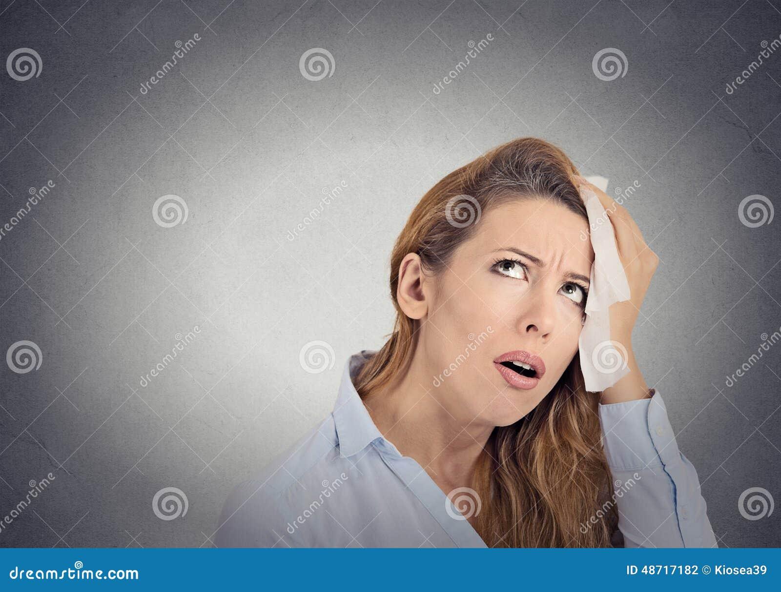 De vermoeide ongerust gemaakte vrouw veegt zweet op haar gezicht af