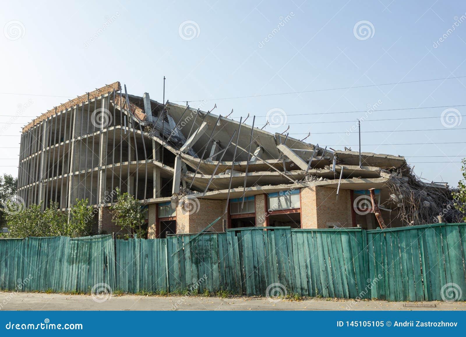De vernietigde bouw achter een groene omheining