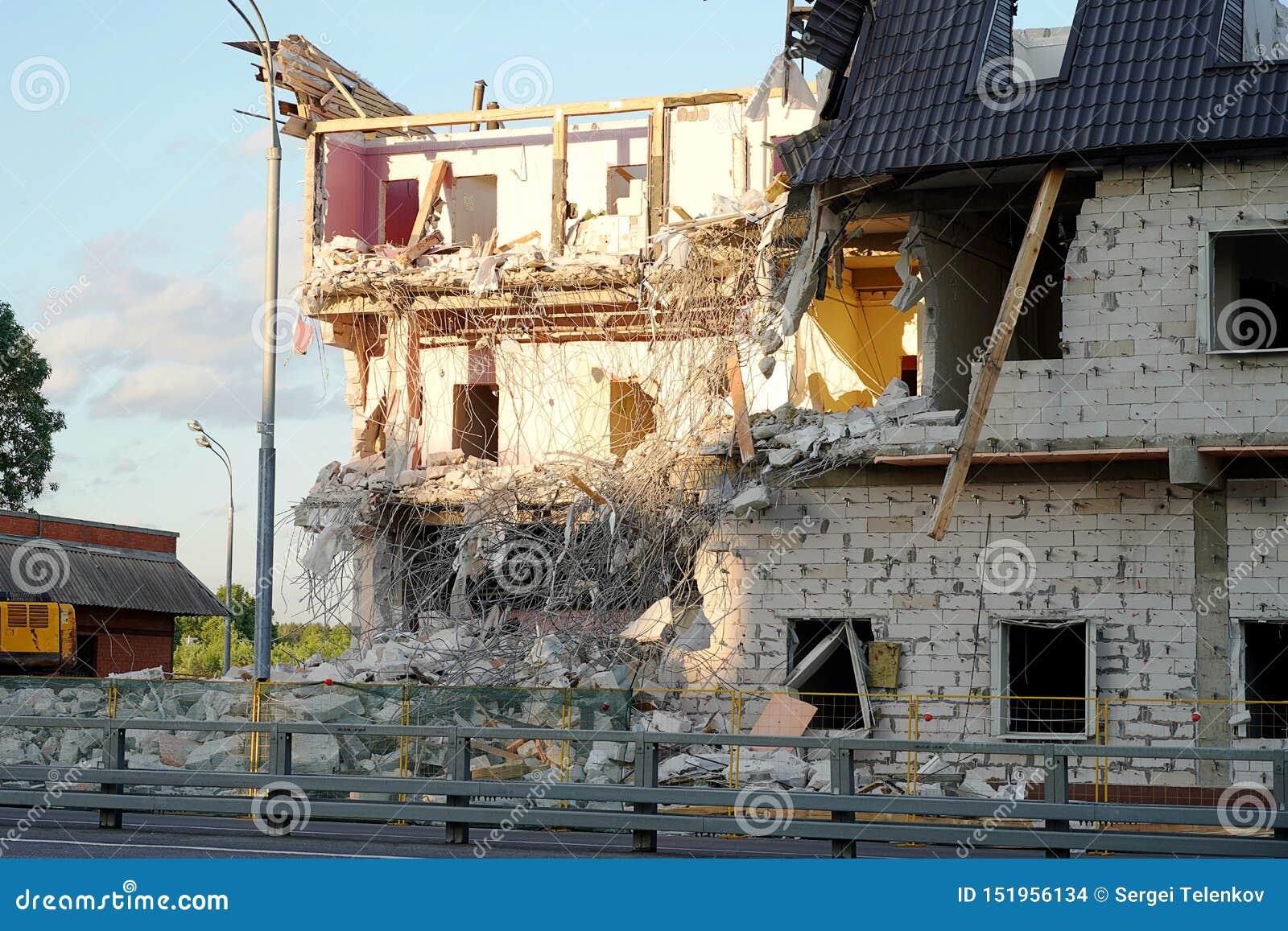 De vernietiging van een gebouw met meerdere verdiepingen De vloeren en de muren worden vernietigd, montage, concrete blokken, hou