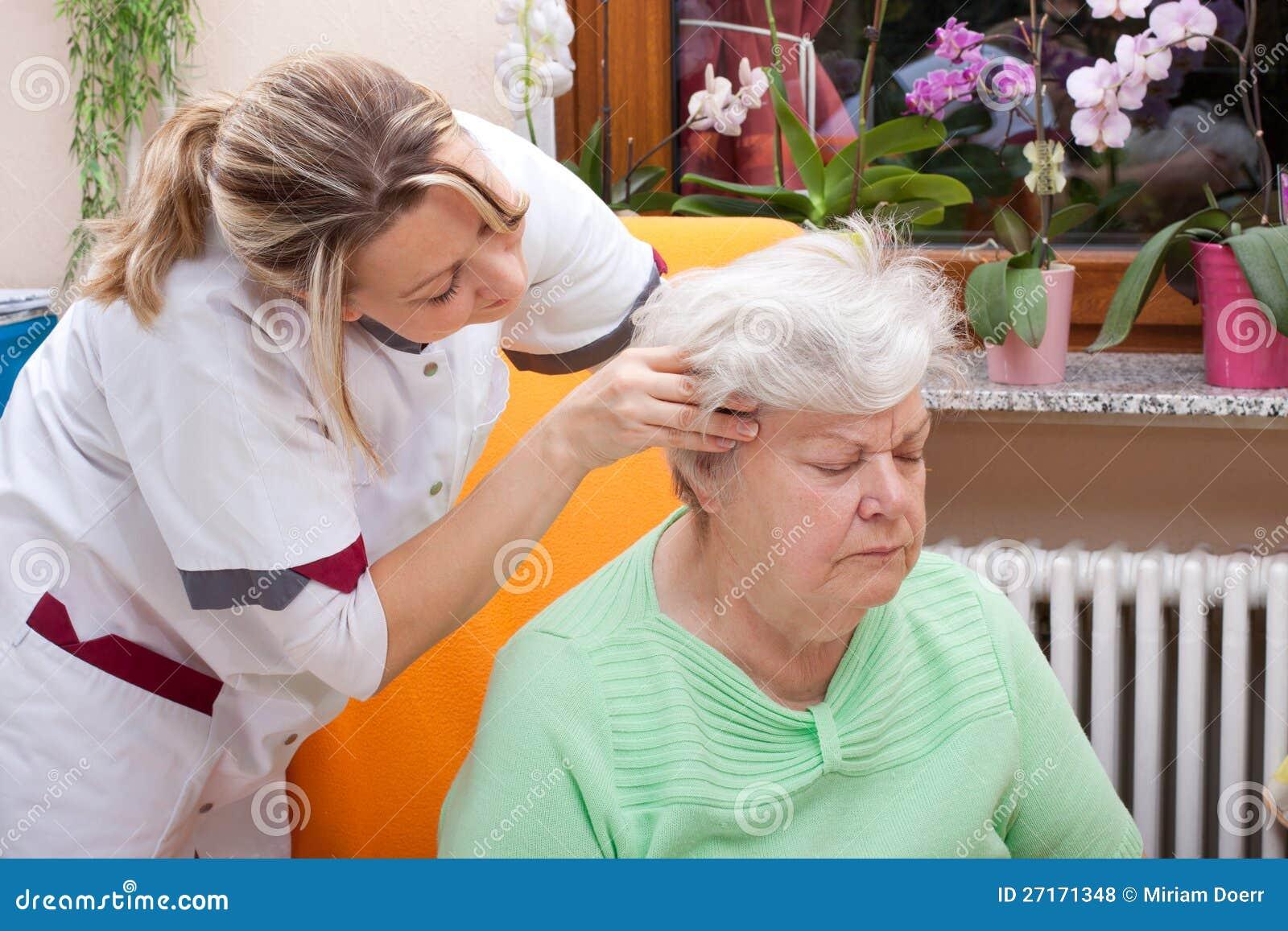 De verpleegster masseert het hoofd van een oudste
