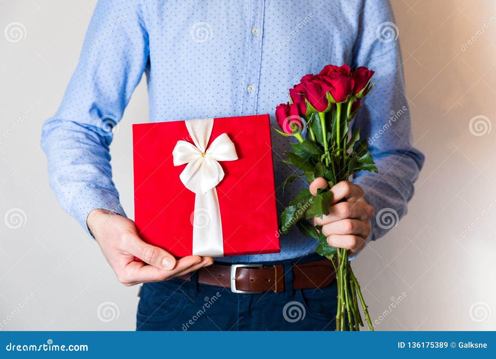 De verrassing van de valentijnskaartendag, liefde die, knappe mens romantische gift en rood rozenboeket houden