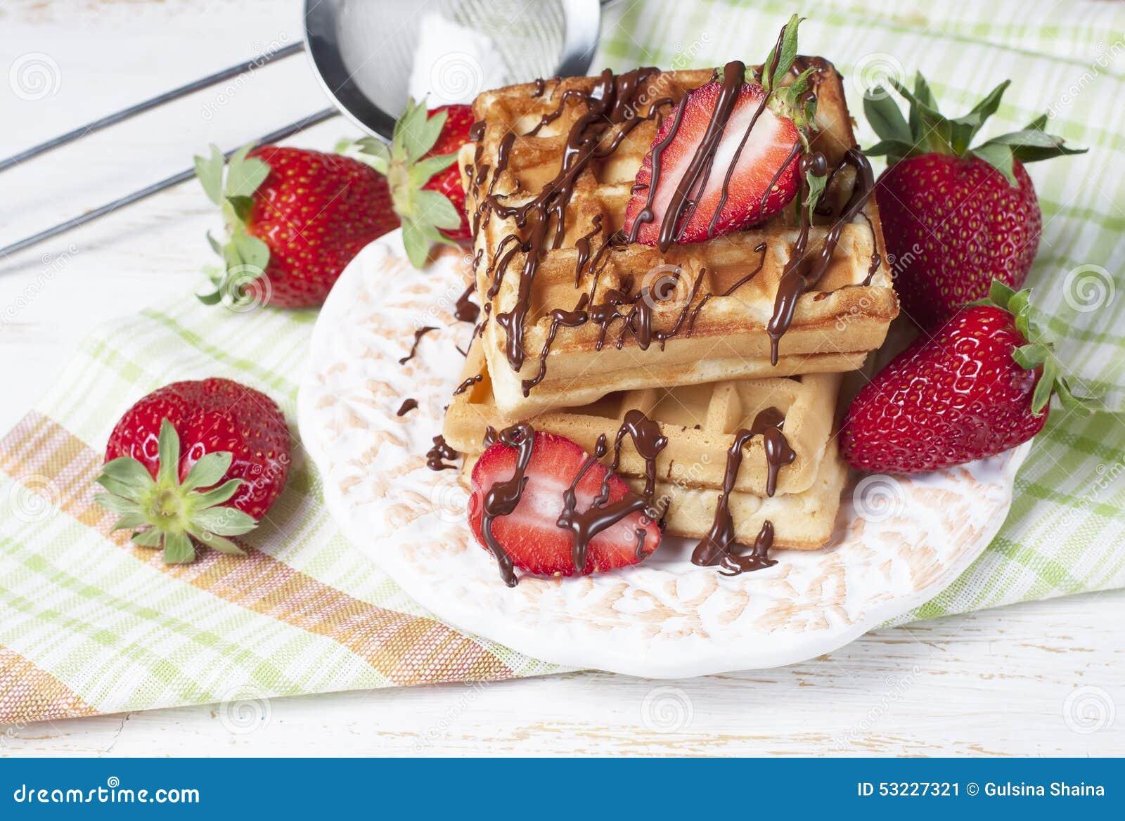 De vers gebakken wafels van België met chocoladesaus en strawberr