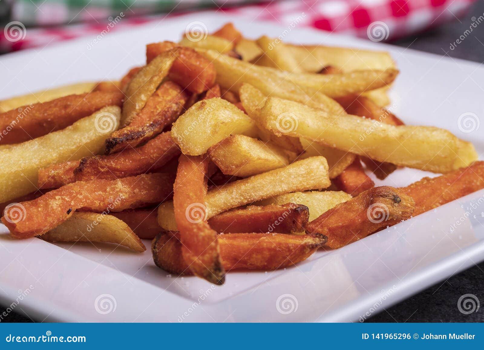 De verscheidenheid van aardappels voor versiert: frieten en bataat op een plaat