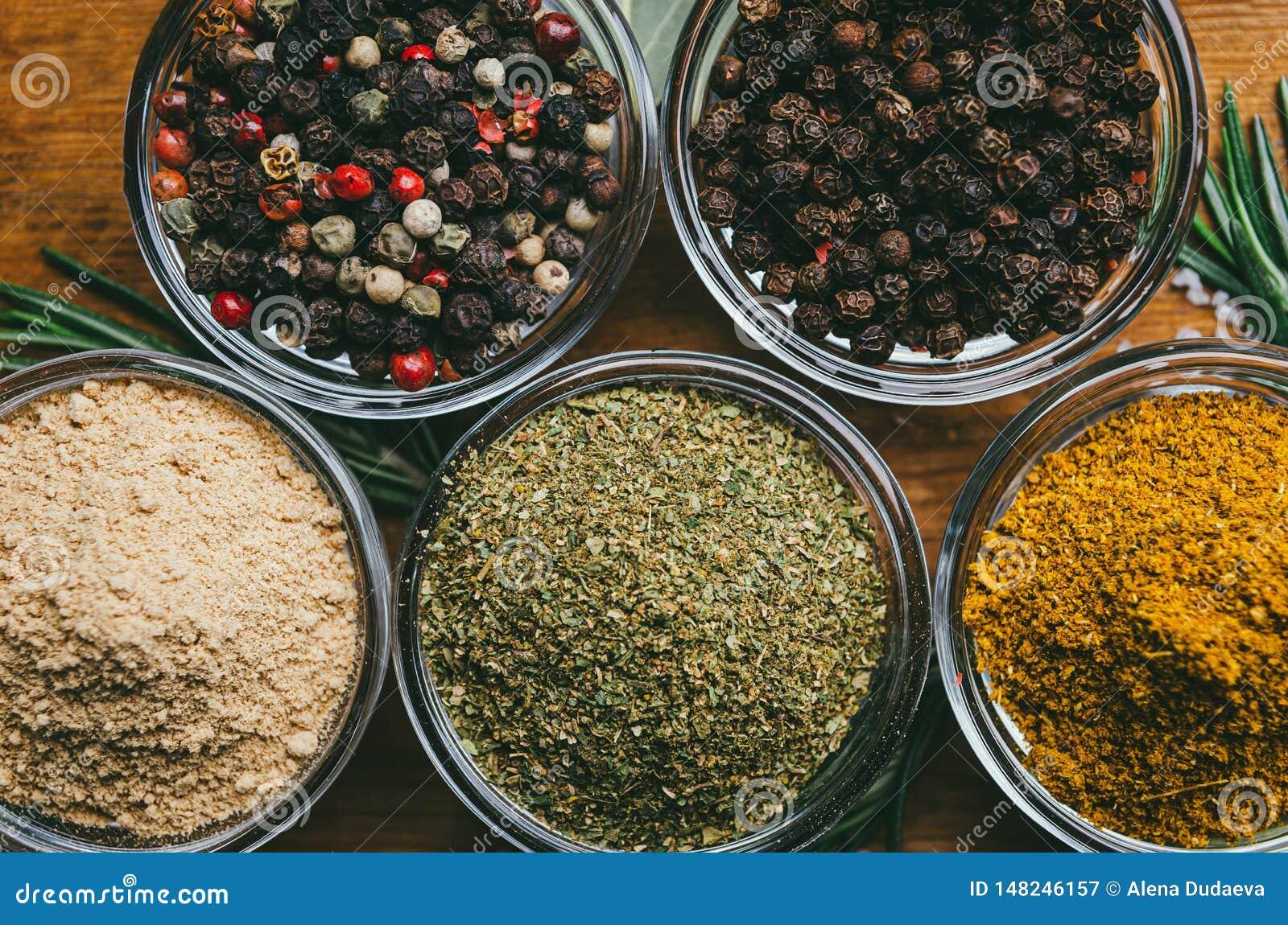 De verscheidenheid van kruiden in rond glas werpt - gemalen gember, hop-suneli, Kari, zwarte peper en een mengsel