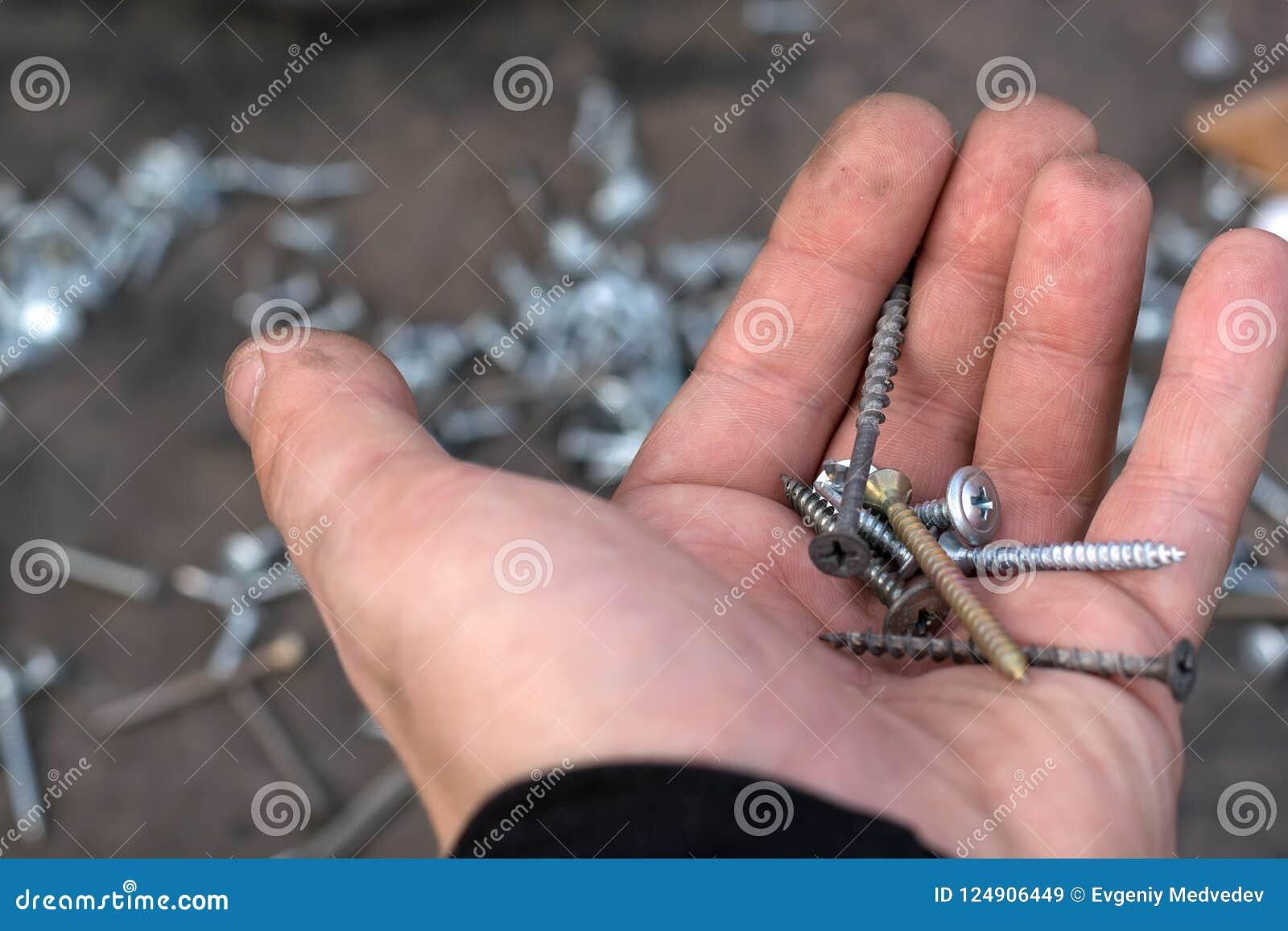 De verschillende metaalschroeven liggen in de palm van de werkende man