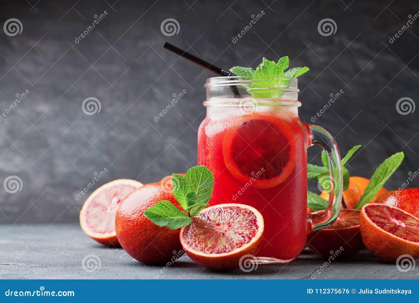 De verse oranje limonadedrank of het sap verfraaide muntbladeren in de kruik van het metselaarglas op zwarte achtergrond