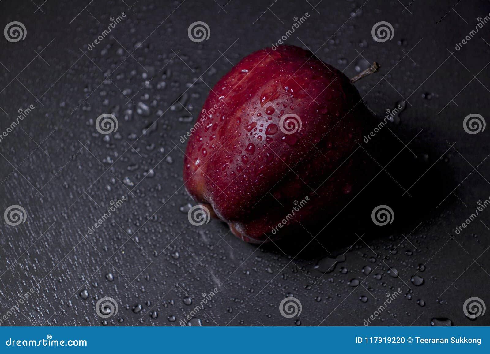 De verse rode appel met druppeltjes van water en heeft licht