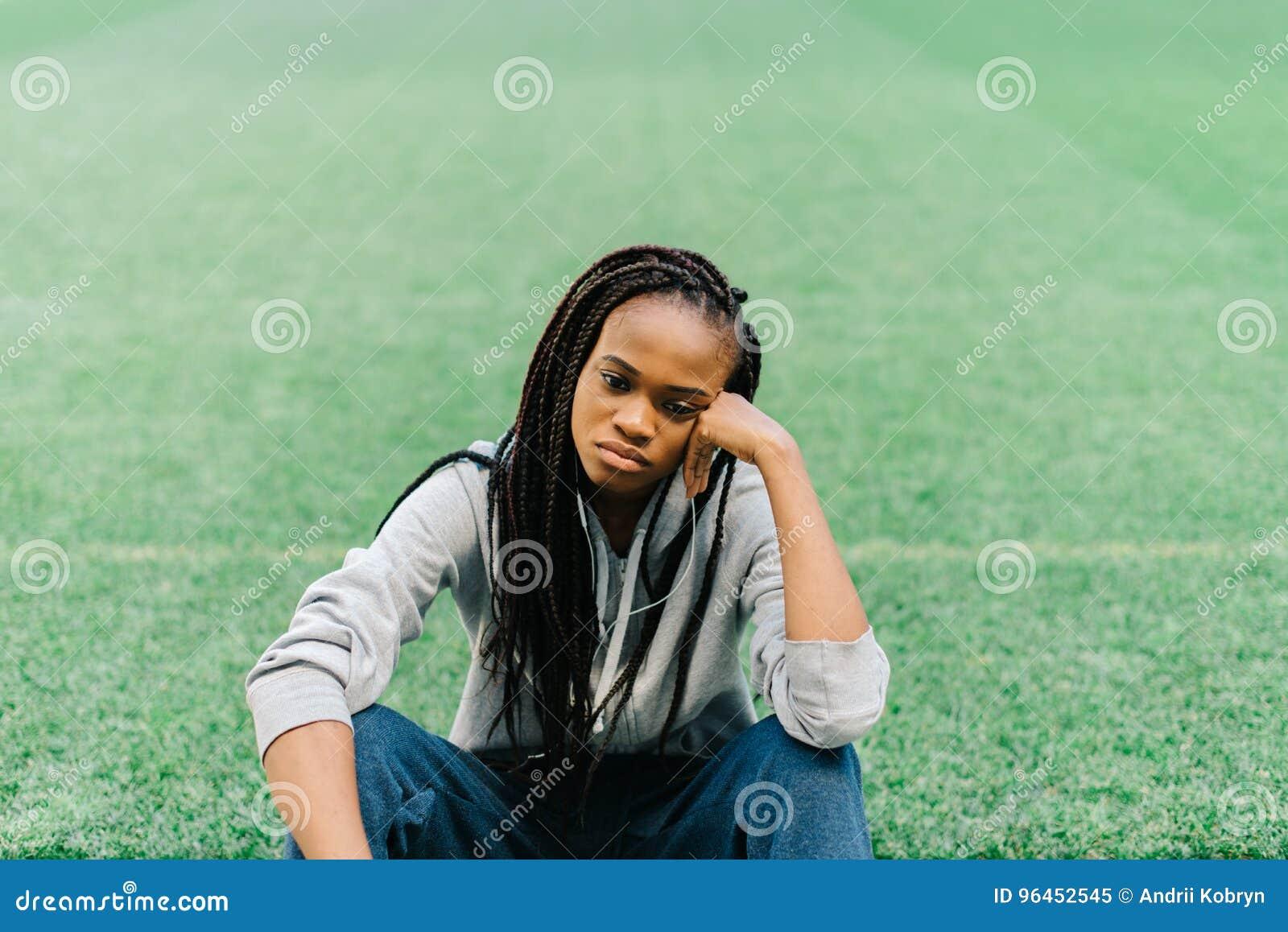 De verstoorde Afro-Amerikaanse tiener zit op het gras en leunt op haar hand