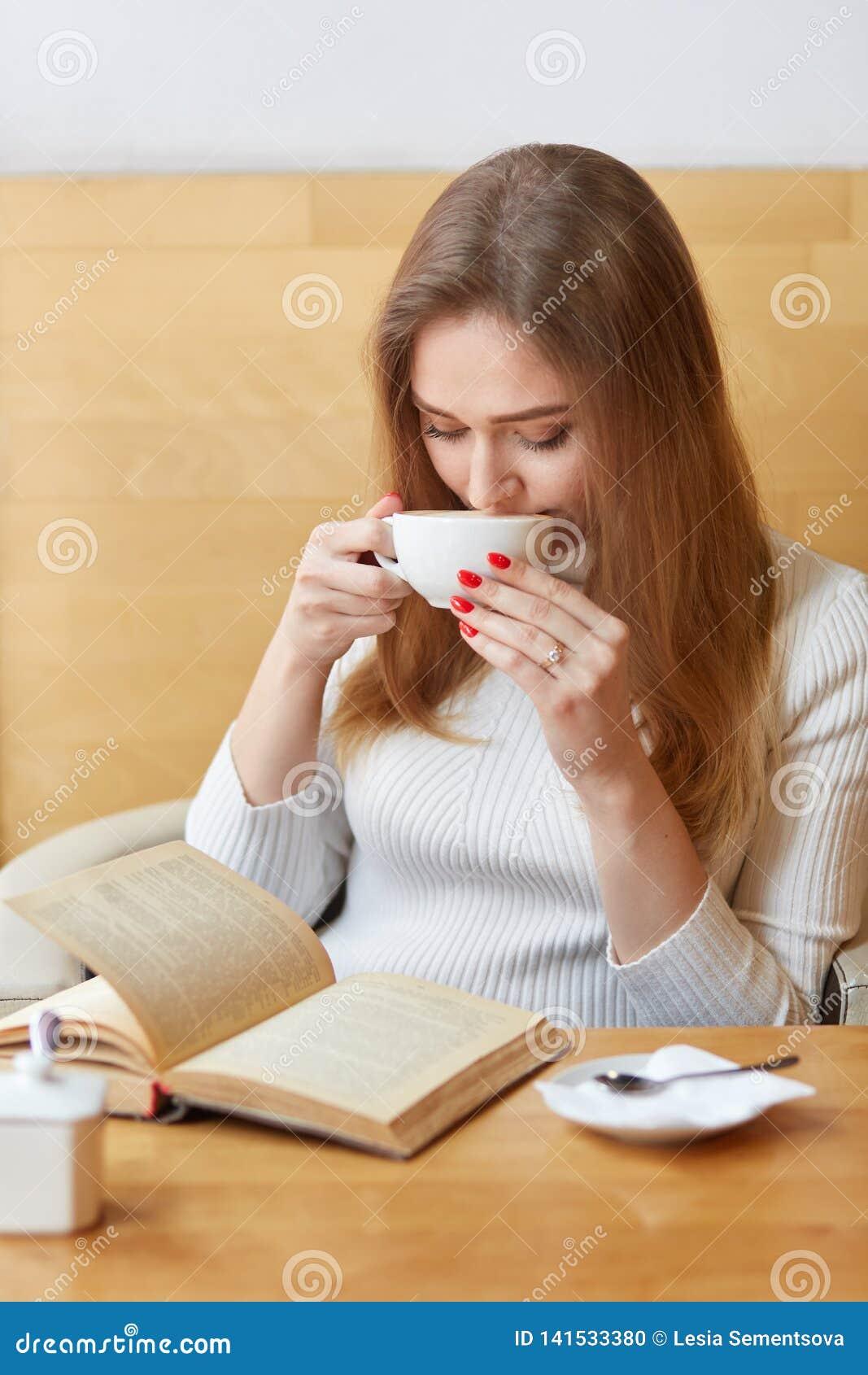 De verticaal van onbezorgde mooie vrouw wordt geschoten de dranken hete thee van witte mok, fantastisch verhaal leest, houdt van
