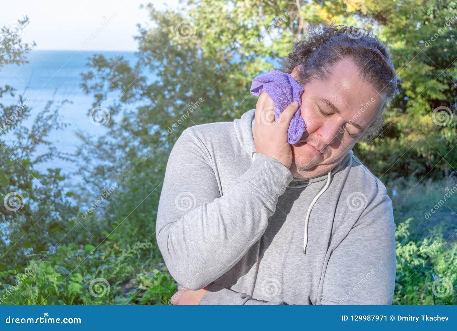 De vette mens veegt zijn gezicht met een handdoek af die zich op de oceaan bevinden sport en een gezonde levensstijl