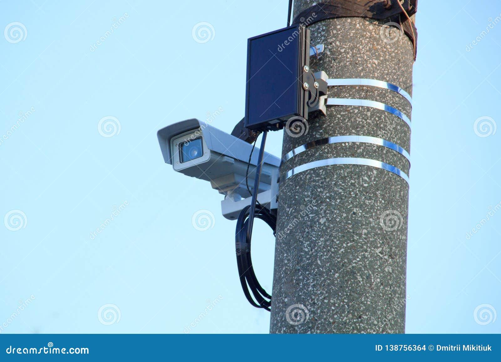 De videocamera in het verzegelde thermische jasje op de steun wordt bevestigd op een betonwegpijler