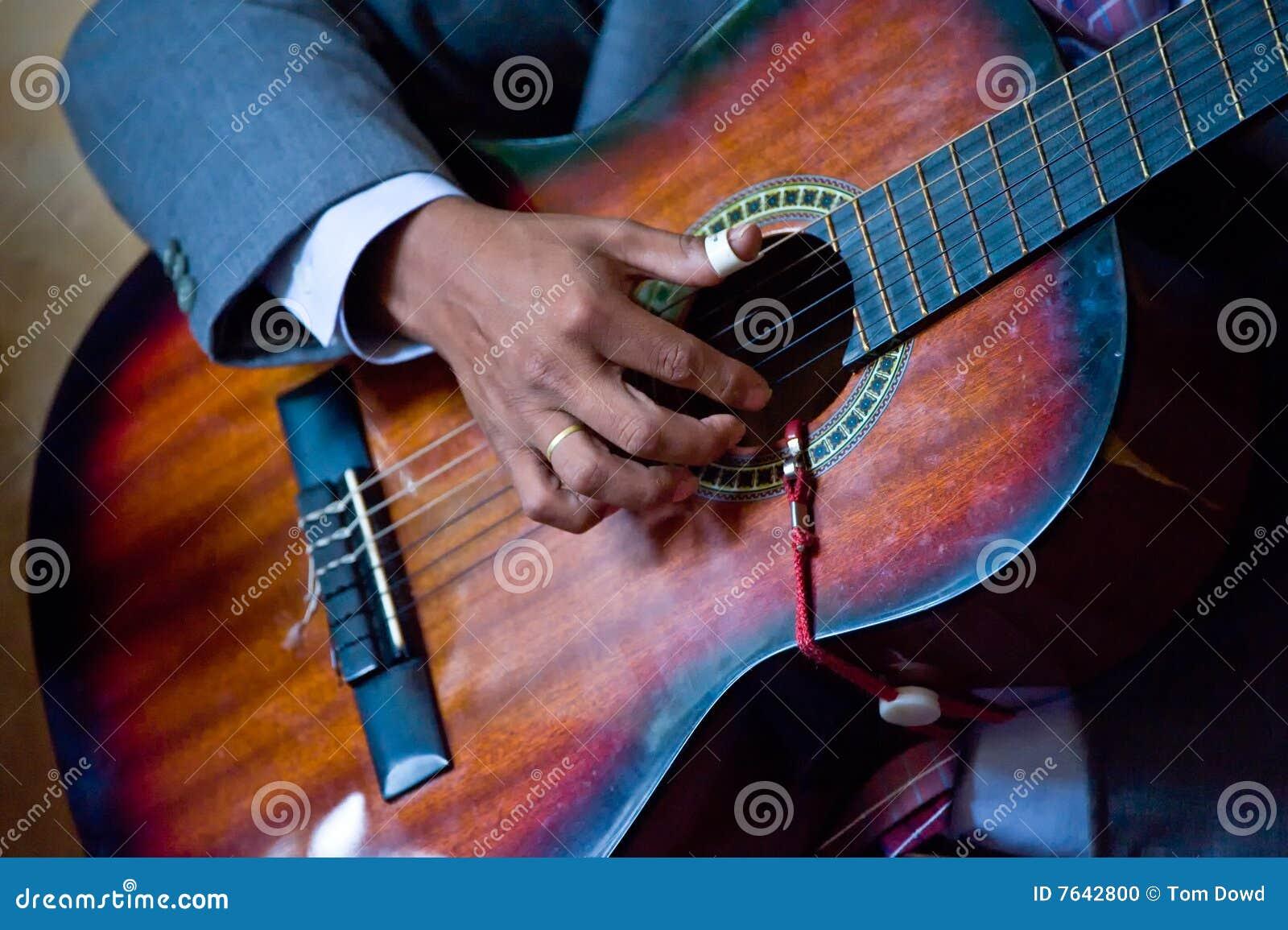 De vinger van de persoon het plukken gitaar