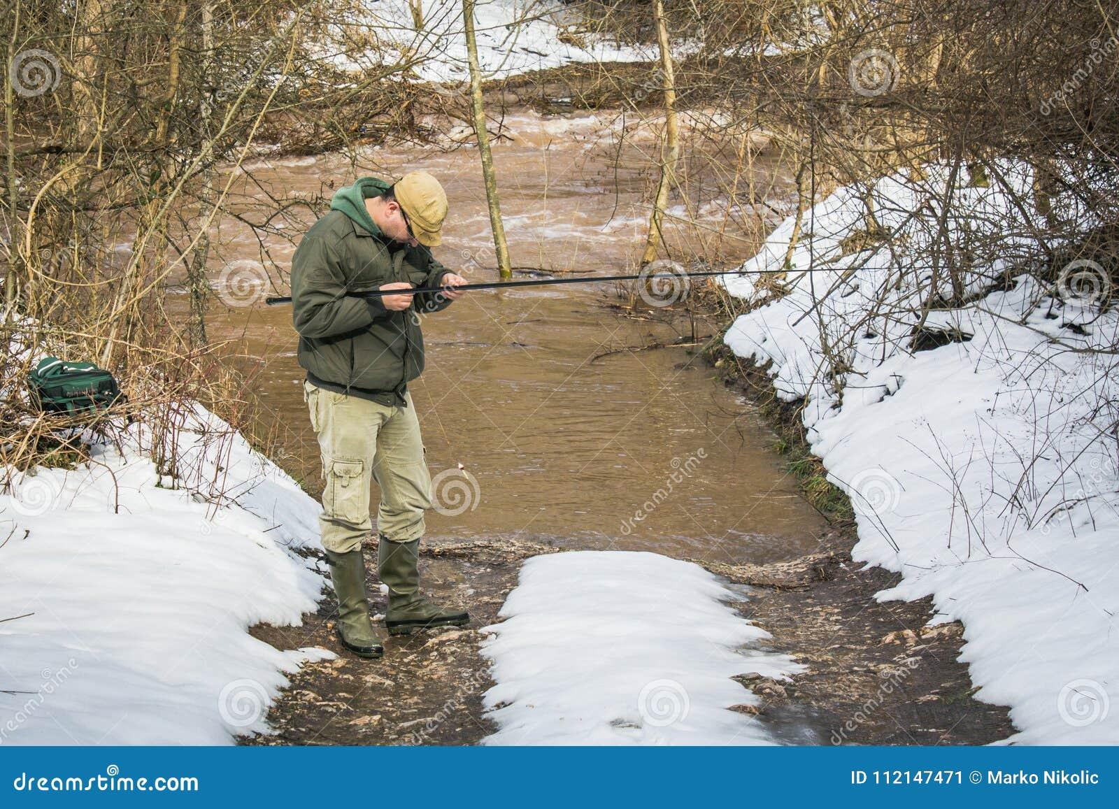 De visser probeert om vissen in de rivier te vangen