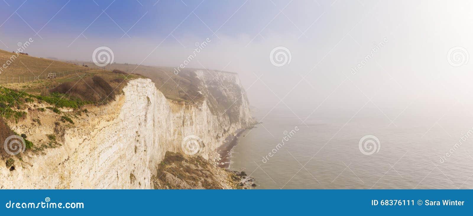 De vita klipporna av Dover på en dimmig morgon