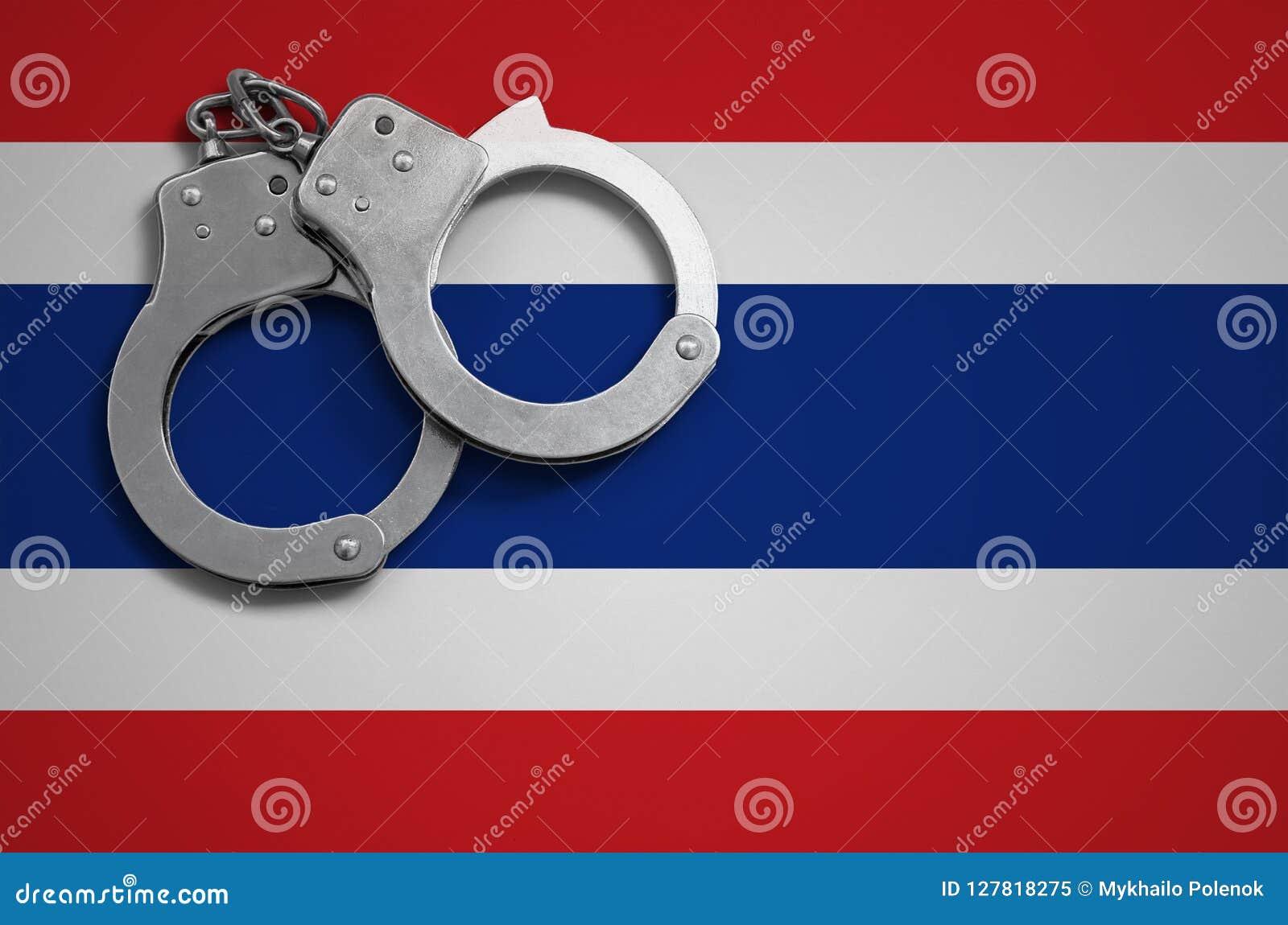 De vlag en de politiehandcuffs van Thailand Het concept misdaad en inbreuken in het land