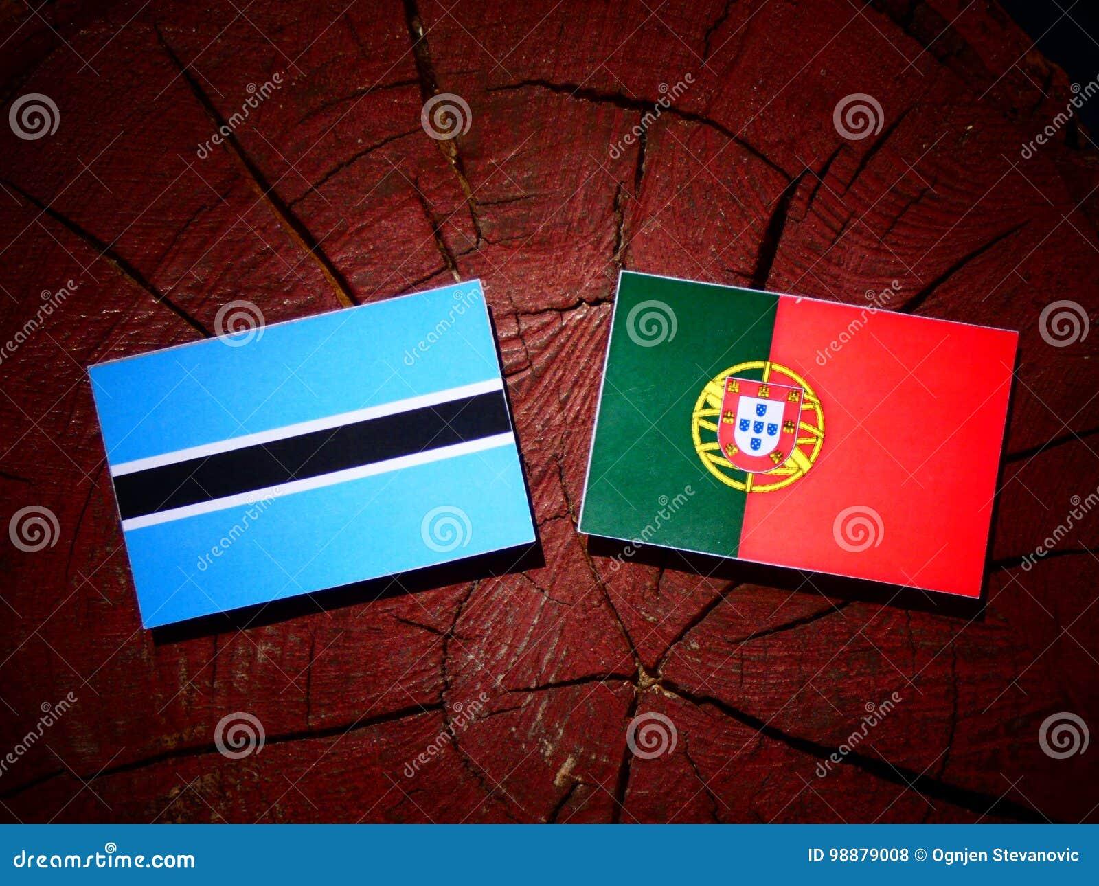 De vlag van Botswana met Portugese vlag op een geïsoleerde boomstomp