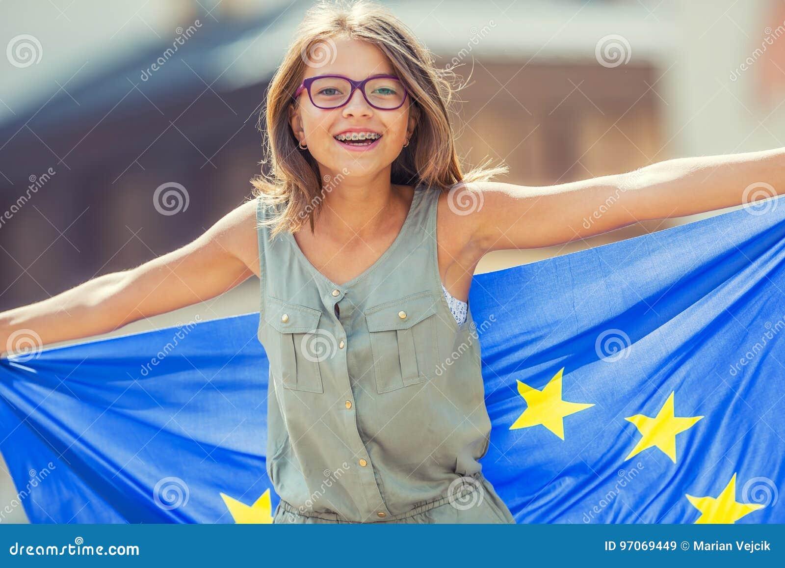 De vlag van de EU Leuk gelukkig meisje met de vlag van de Europese Unie Jonge tiener die met de Europese Unie vlag in de stad gol