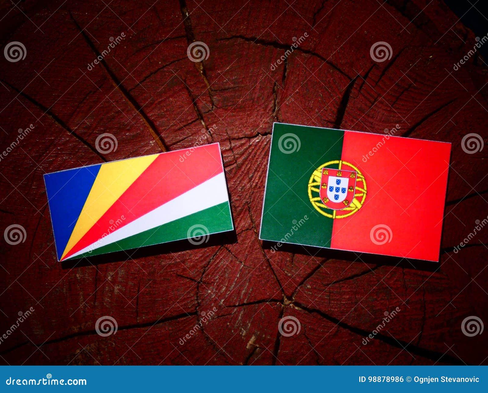 De vlag van Seychellen met Portugese vlag op een geïsoleerde boomstomp