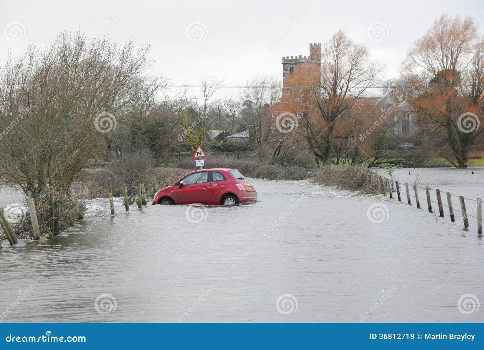 De vloed overspoelt rode auto