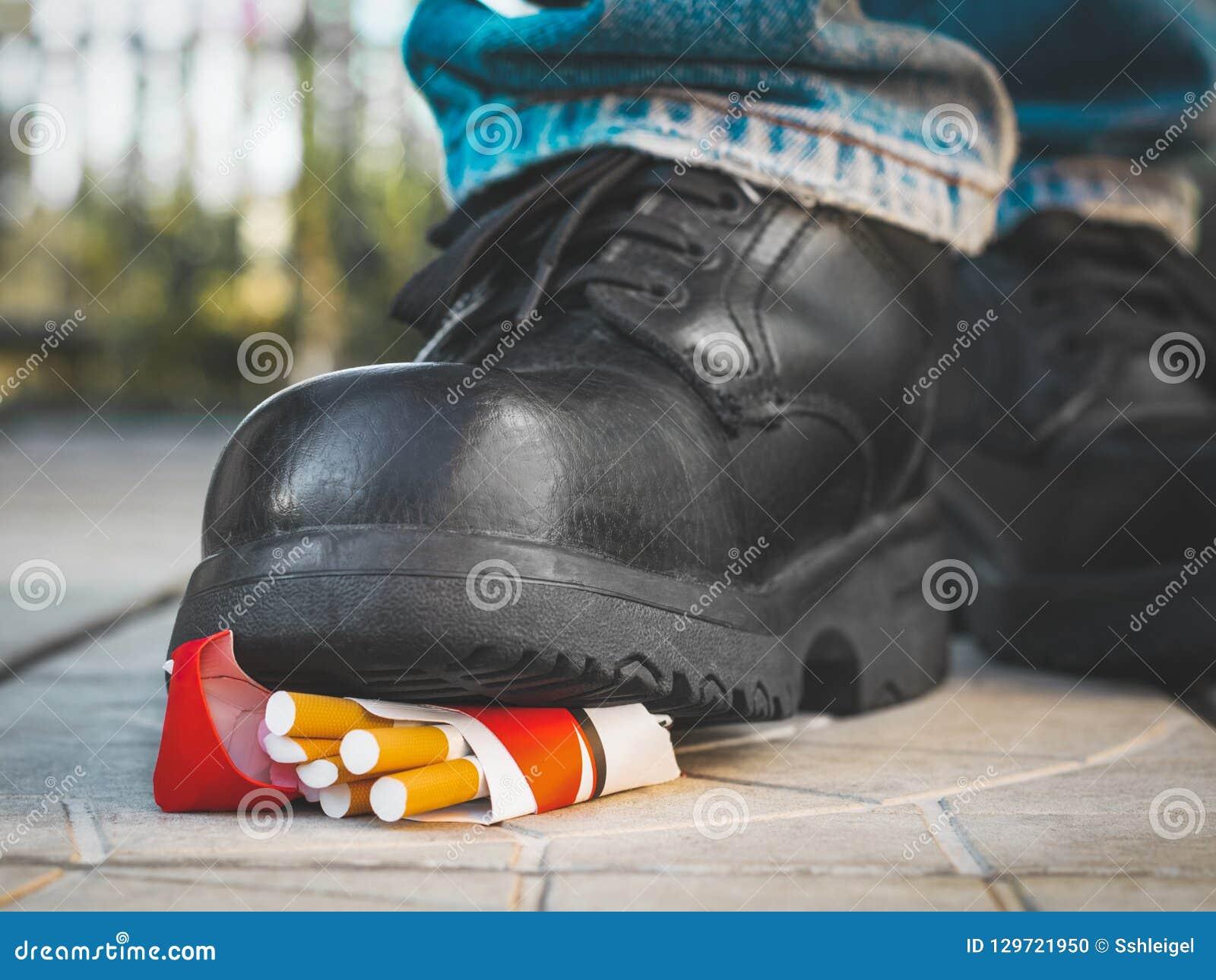 De voet in een zwarte laars verplettert een pak sigaretten