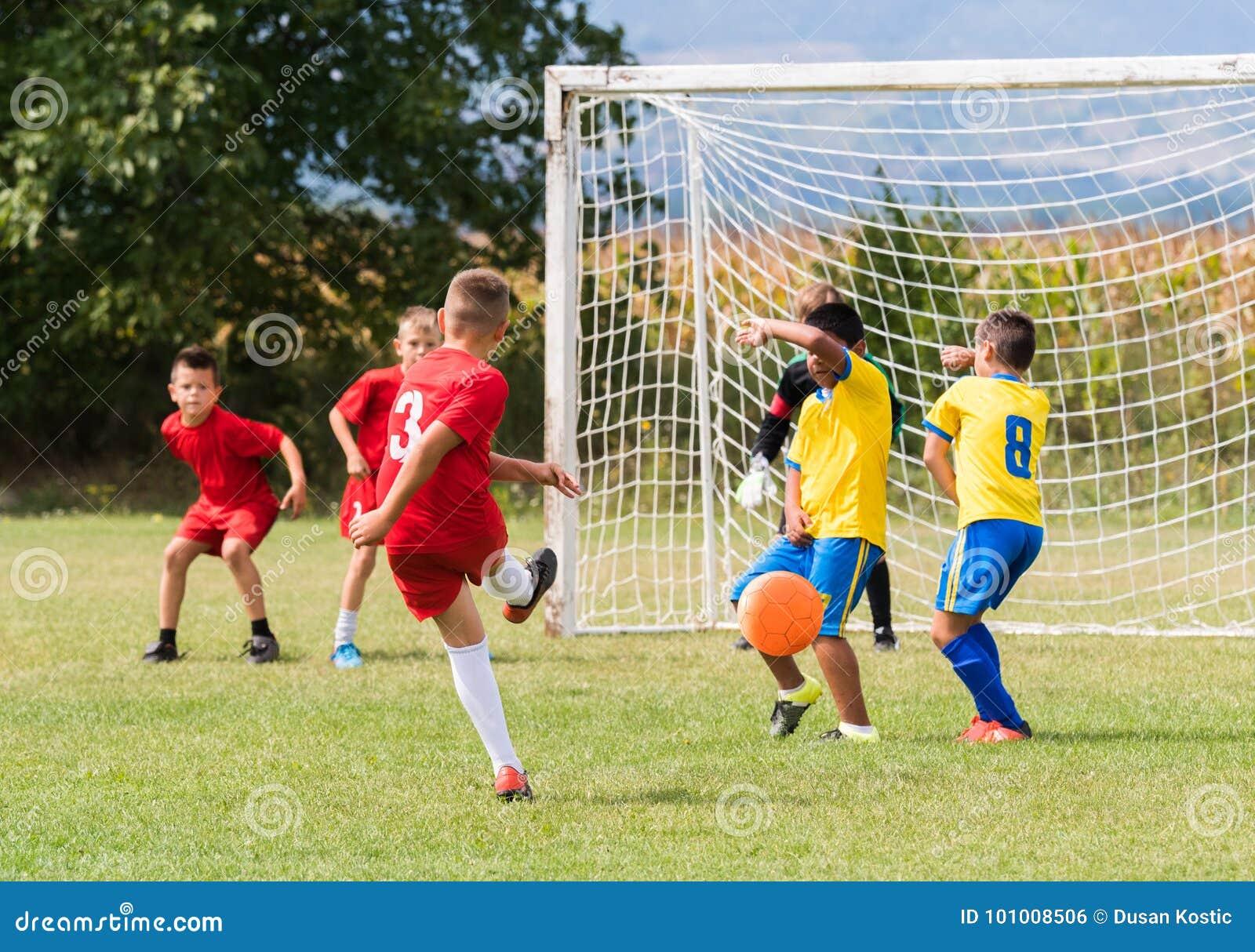 De voetbal van het jonge geitjesvoetbal - de gelijke van kinderenspelers op voetbalgebied