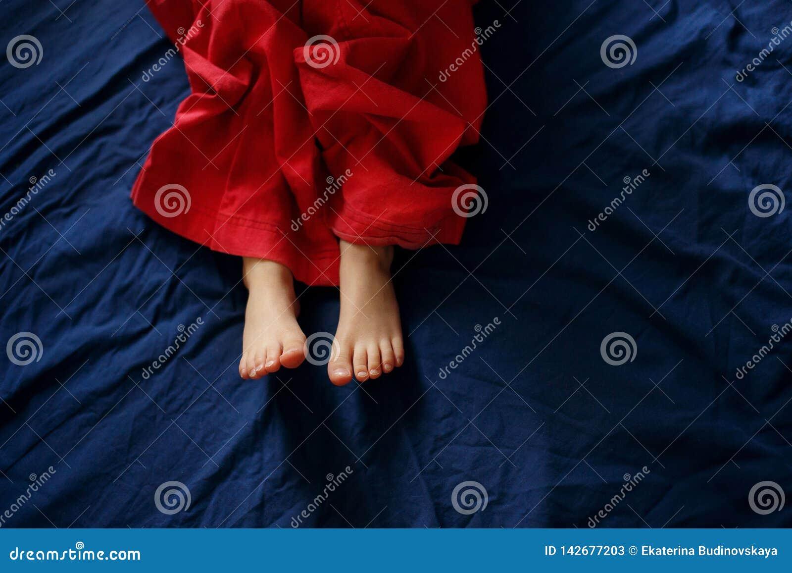 De voeten van de baby op het bed
